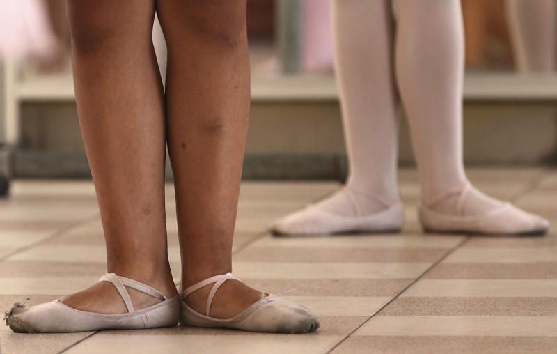 In this April 2, 2019 photo, young ballet students stand in first position in a dance studio at a public school in the Chorrillos neighborhood, a poor part of Lima, Peru. A former National Ballet of Peru dancer is bringing classical ballet dancing to children from impoverished communities where leotards and shiny pink pointe shoes are seldom if ever seen. (AP Photo/Martin Mejia)