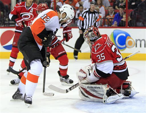 Philadelphia Flyers' Simon Gagne (12) has his shot blocked by Carolina Hurricanes goalie Justin Peters (35) during the first period of an NHL hockey game, Saturday, April 20, 2013, in Raleigh, N.C. (AP Photo/Karl B DeBlaker)