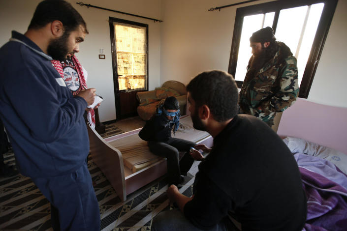 In this Friday, Dec. 14, 2012, photo, Syrian rebels question a suspected motorcycle thief, at their headquarters, in Maaret Misreen, near Idlib, Syria. The town is broke, relying on a slowing trickle of local donations. The rebels, a motley crew of laborers, mechanics and shopowners, have little experience in government. President Bashar Assad's troops still control the city of Idlib a few miles away, making area roads unsafe and keeping Maaret Misreen cut off from most of Syria.(AP Photo/Muhammed Muheisen)