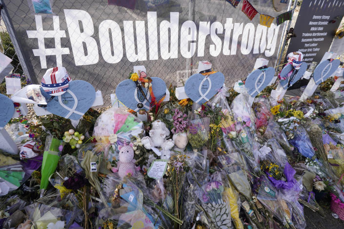 Tributes stand near the temporary fence surrounding the parking lot in front of a King Soopers grocery store in which 10 people died in a late March mass shooting Friday, April 9, 2021, in Boulder, Colo. (AP Photo/David Zalubowski)