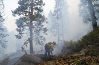 Will Fitch, fire captain from Cosumnes Fire Department, holds a fire line to keep the Caldor Fire from spreading in South Lake Tahoe, Calif., Friday, Sept. 3, 2021. Fire crews took advantage of decreasing winds to battle a California wildfire near popular Lake Tahoe and were even able to allow some people back to their homes but dry weather and a weekend warming trend meant the battle was far from over.(AP Photo/Jae C. Hong)