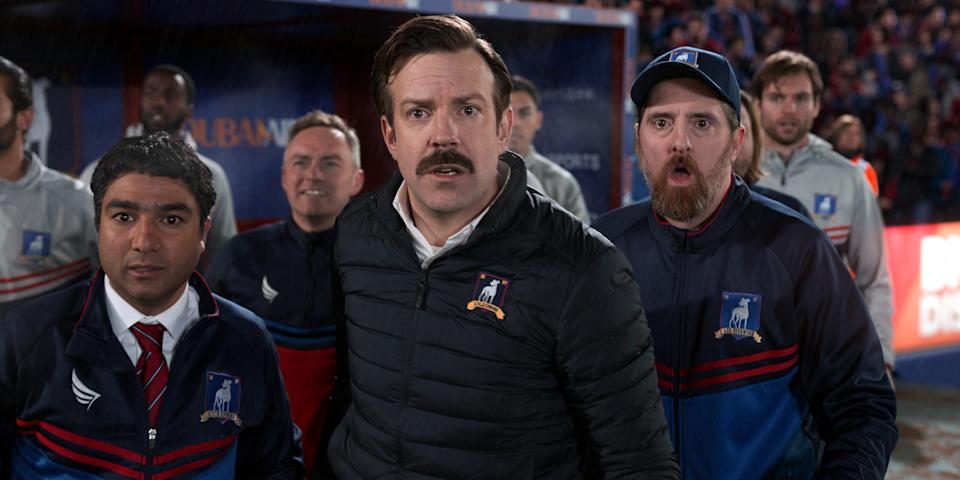 """Nate (Nick Mohammed), Ted (Jason Sudeikis) and Beard (Brendan Hunt) take in a different kind of football in Apple TV+'s """"Ted Lasso."""""""