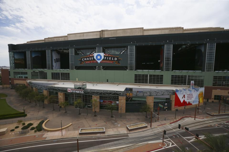 FILE - This Thursday, March 26, 2020 file photo shows Chase Field in Phoenix, the home of the Arizona Diamondbacks, which has been empty because of the coronavirus pandemic as the baseball season was shut down. Putting all 30 teams in the Phoenix area this season and playing in empty ballparks was among the ideas discussed Monday, April 6, 2020 during a call among five top officials from MLB and the players' association that was led by Commissioner Rob Manfred, people familiar with the discussion told The Associated Press. (AP Photo/Ross D. Franklin, File)