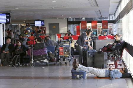 Passengers rest and wait for their flights at the departure area inside the international airport of Santiago