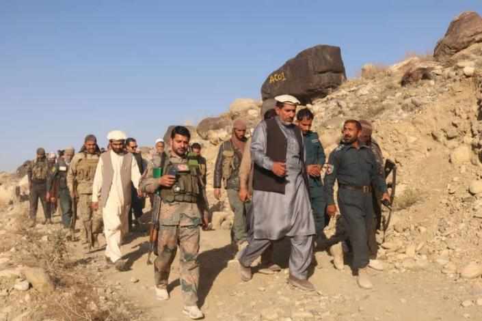 Nangarhar provincial official Ajmal Omar walks with soldiers from the government of former President Ashraf Ghani in this undated photo