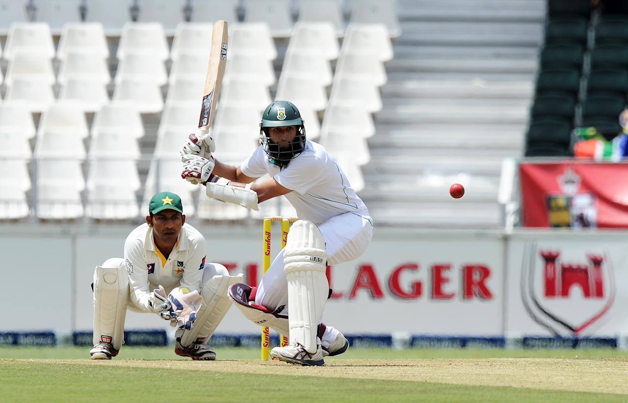South Africa's Hashim Amla bats in front of Pakistan's Sarfraz Ahmed  on February 1, 2013 during the first Test at Wanderers Stadium in Johannesburg.                AFP PHOTO / STRINGER        (Photo credit should read -/AFP/Getty Images)