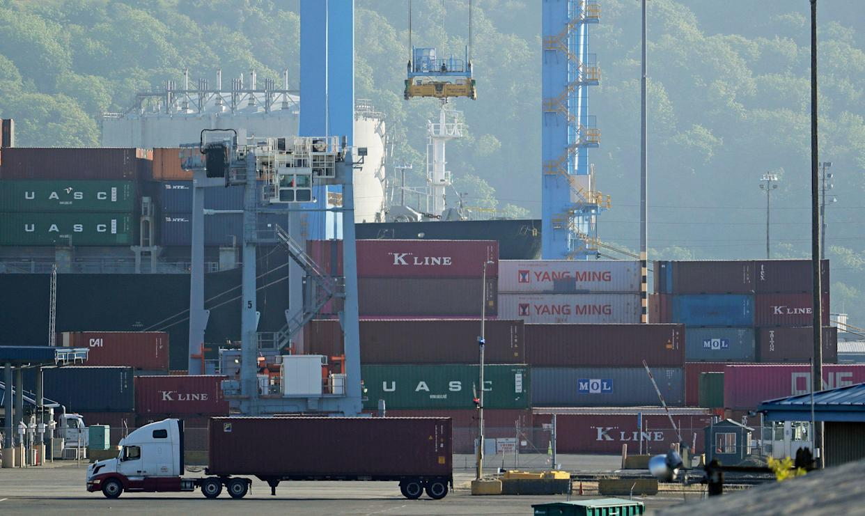 A truck drives near cargo containers, Friday, May 10, 2019, at the Port of Tacoma in Tacoma, Wash. U.S. and Chinese negotiators resumed trade talks Friday under increasing pressure after President Donald Trump raised tariffs on $200 billion in Chinese goods and Beijing promised to retaliate. (AP Photo/Ted S. Warren)
