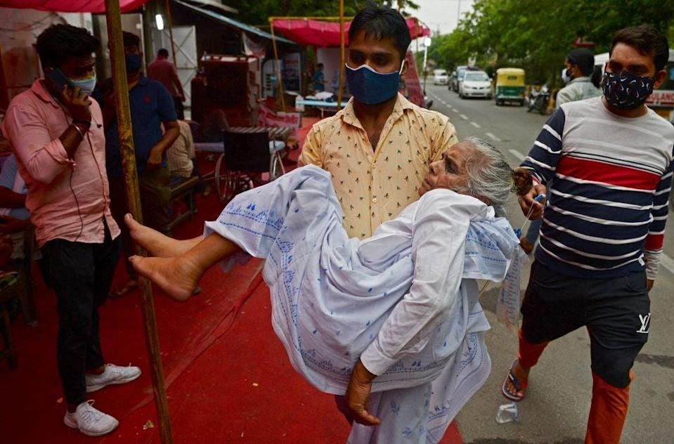 <p>A family member carries a patient, who is having difficulty in breathing, to a free oxygen support centre being run by a Gurdwara, a place of worship for Sikhs, on the outskirts of New Delhi on 10 May</p> (AFP/Getty)