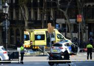 <p>A policemen and a medical staff member stand past police cars and an ambulance in a cordoned off area after a van ploughed into the crowd, injuring several persons on the Rambla in Barcelona on August 17, 2017. (Josep Lago/AFP/Getty Images) </p>