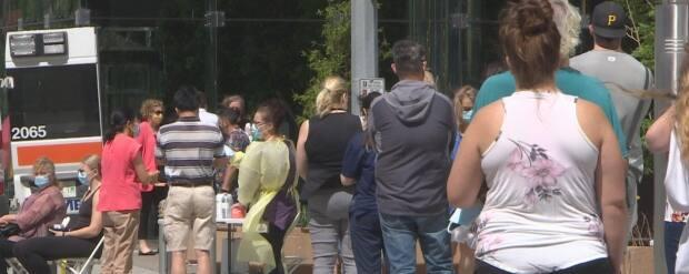 People in Regina line up for their vaccine at a mobile clinic in Regina. Health officials are urging people to get both shots to guard against variants, including the more contagious delta variant. (Matt Howard/CBC - image credit)