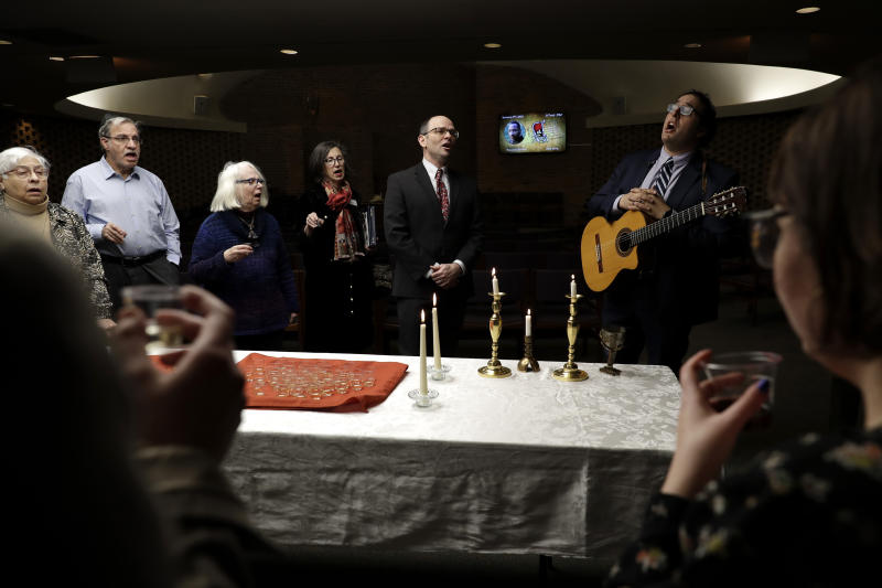In this Jan. 17, 2020, photo Cantor David Berger, right, sings a song with members of KAM Isaiah Israel during the Friday Shabbat Service at KAM Isaiah Israel in Chicago. On the eve of the day set aside to honor an African American who strove against hate and preached racial and social justice, some worry the nation is becoming more divided. (AP Photo/Nam Y. Huh)