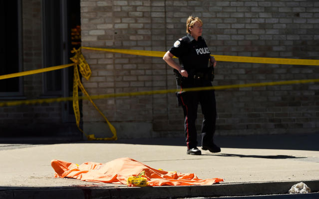 <p>A police officer stands over a covered body in Toronto after a van mounted a sidewalk crashing into a number of pedestrians on Monday, April 23, 2018. (Photo: Nathan Denette/Canadian Press) </p>