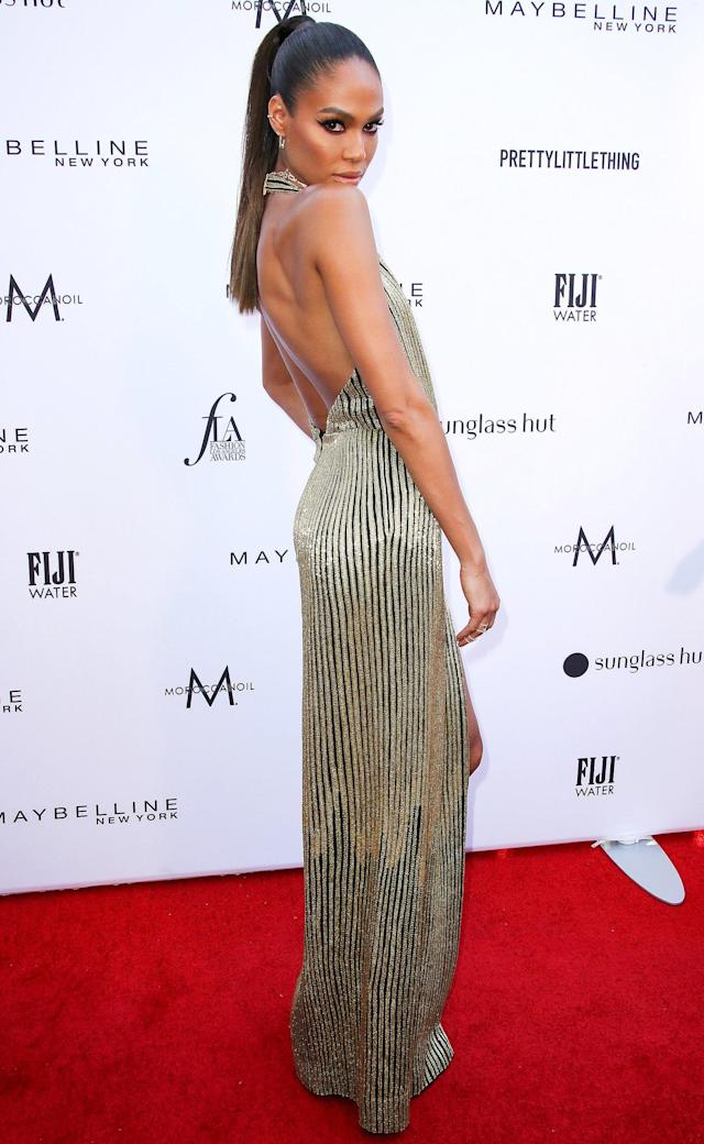a9b81871b5 in a Oscar de la Renta striped gold halter gown with a thigh high slit and