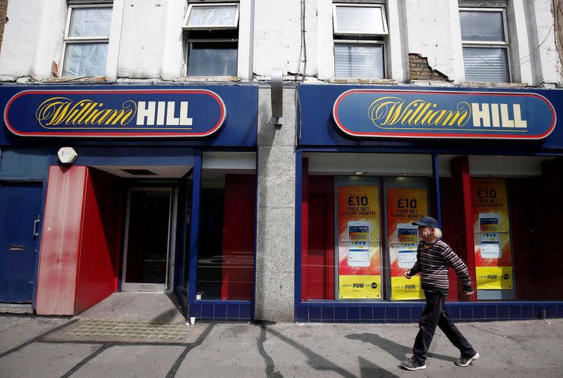 FILE PHOTO: A pedestrian walks past a William Hill betting shop in London