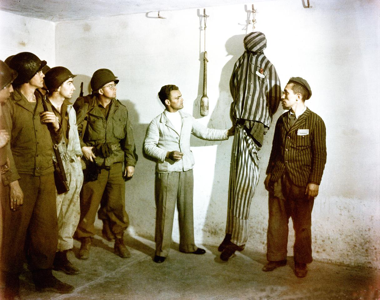 Concentration Camp Buchenwald, In the crematorium cellar mortuary, former prisoners demonstrate to a group of American GIs how inmates were hanged from hooks in the wall. 18th April1945. Germany. Photo by Ardean R. Miller. (Photo by Galerie Bilderwelt/Getty Images)