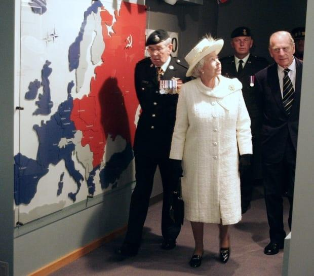 Queen Elizabeth II and Prince Philip are framed by a Second World War display while visiting the Museum of the Regiments in Calgary on Wednesday, May 25, 2005. The Queen and Prince viewed various displays showing the history of Alberta regiments. (CP PHOTO/POOL-Andy Clark)