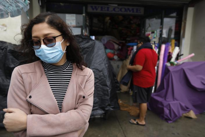 Charm Resuello, 26, wears a surgical mask to ward off Covid-19, while shopping for flowers in the Flower District in downtown Los Angeles on March 10, 2020. (Genaro Molina / Los Angeles Times)