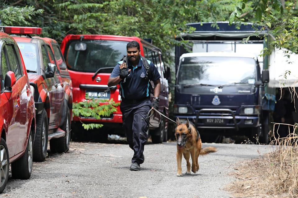 A police officer uses a sniffer dog as police search for 15-year-old Irish girl Nora Anne Quoirin who went missing from a resort in Seremban, Malaysia.