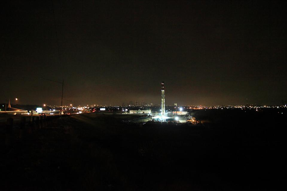 FORT WORTH, TX - DECEMBER 16: A 150-foot derrick towers over traffic along Interstate 35W, left, positioned on a natural gas well site on December 16, 2008 in Fort Worth, Texas. The well, with a view of the Fort Worth skyline, is owned by the Chesapeake Energy Corporation with mineral rights leased from a local landowner. (Photo by Robert Nickelsberg/Getty Images)