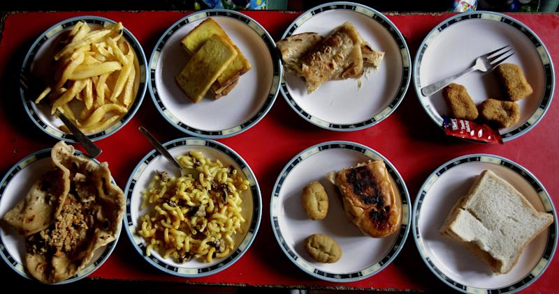 "Assorted lunch plates are arranged at a table for students at the Bahria Foundation school in Rawalpindi, Pakistan, Tuesday, May 6, 2014. Most of the kids seen there have home cooked food for lunch. Principal Syeda Arifa Mohsin says the school tries to dissuade parents from fixing junk food for their children. ""If we discover that a child has junk food, we ask his or her parents to please make a little effort for their child's health,"" Mohsin says. (AP Photo/Anjum Naveed)"