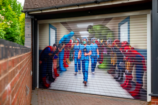 The eye-catching image shows comic book heroes such as Superman, Spider-Man and Batman bowing their heads. (SWNS)