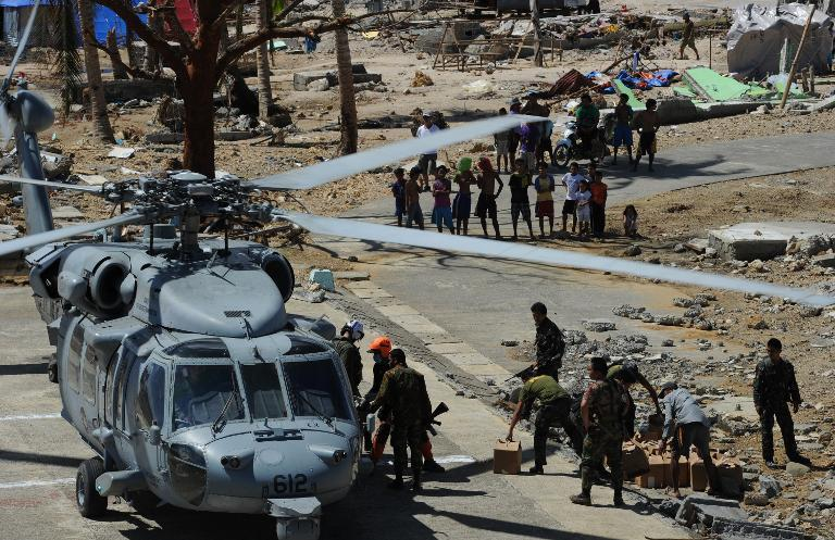 US and Philippines military personnel unload relief food from a US Navy Seahawk helicopter in the town of Hernani, Eastern Samar province in the central Philippines on November 18, 2013, over a week after Super Typhoon Haiyan devastated the area