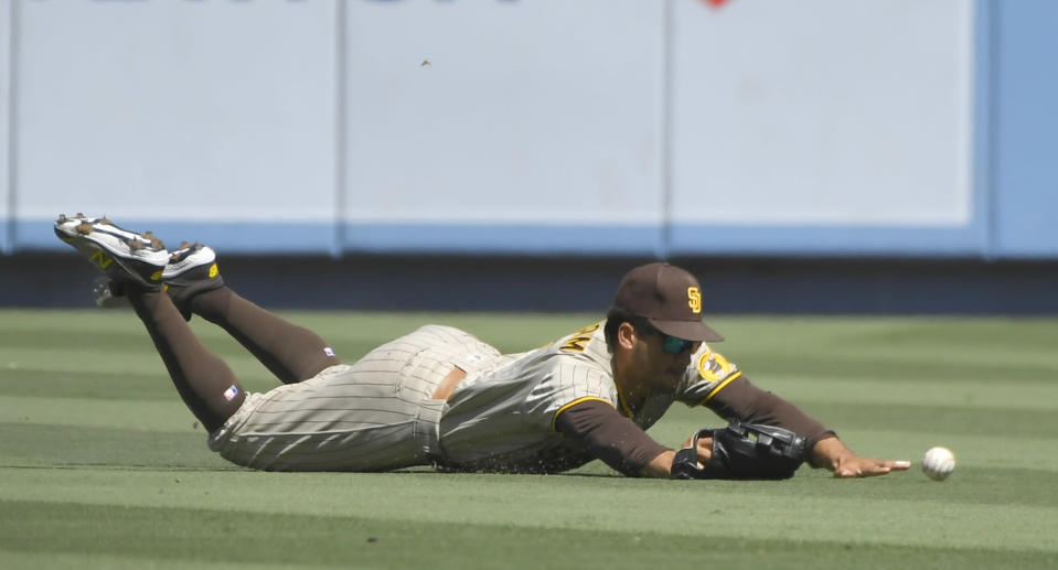 San Diego Padres center fielder Trent Grisham dives but cannot catch a fly ball hit by Los Angeles Dodgers' Trea Turner in the first inning during in a baseball game Sunday, Sept. 12, 2021, in Los Angeles, Calif. (AP Photo/John McCoy)