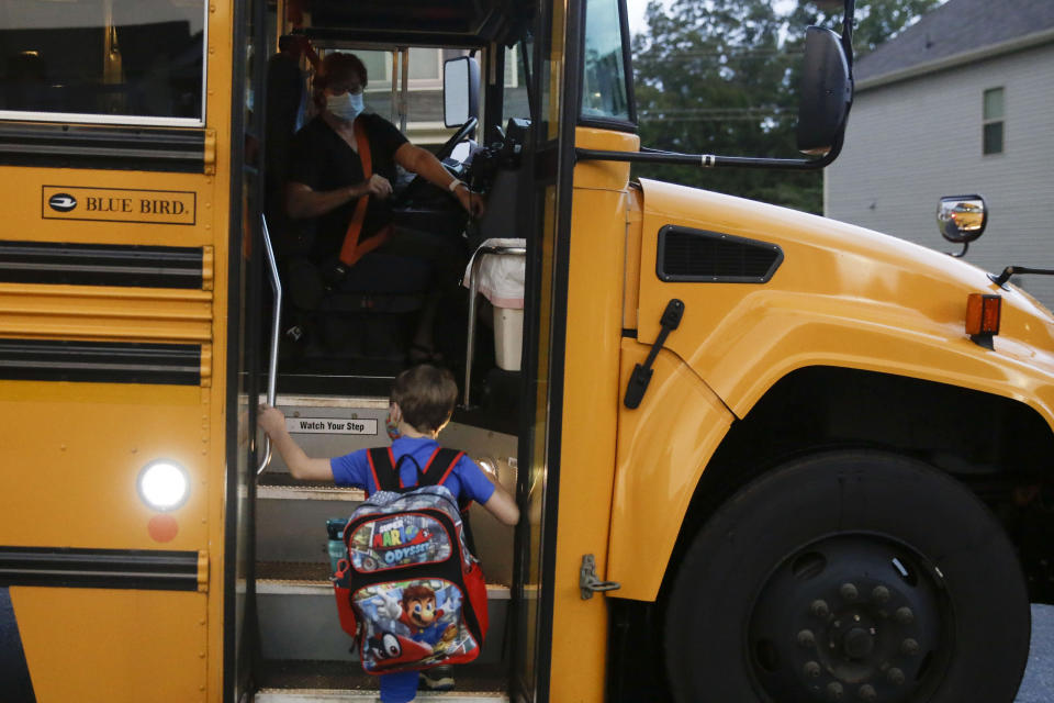 Paul Adamus, 7, climbs the stairs of a bus before the fist day of school on Monday, Aug. 3, 2020, in Dallas, Ga. Adamus is among tens of thousands of students in Georgia and across the nation who were set to resume in-person school Monday for the first time since March. (AP Photo/Brynn Anderson)
