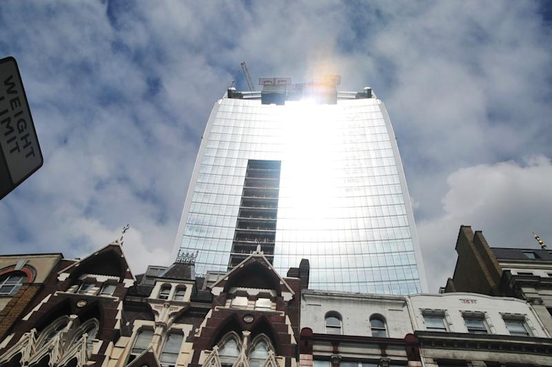 """The 37-storey skyscraper at 20 Fenchurch Street, which is still under construction in the City of London, Tuesday, Sept. 3, 2013. Developers for an unfinished skyscraper in central London say they are investigating the way the building reflects bright sunlight _ after claims that the intense glare melted parts of a car parked nearby. The companies behind the skyscraper, nicknamed the """"Walkie-Talkie"""" because of its curved shape, are responding to complaints from the owner of a Jaguar who told the BBC that the mirror, panels and the Jaguar badge had all melted from the concentrated heat of sunlight reflected from the building. (AP Photo/PA, Andy Scofield) UNITED KINGDOM OUT NO SALES NO ARCHIVE"""