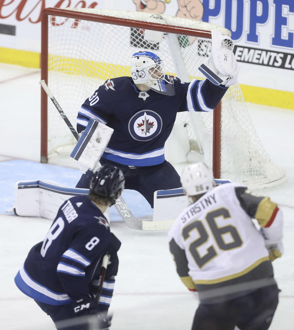 Winnipeg Jets goaltender Laurent Brossoit (30) stops Vegas Golden Knights' Paul Stastny (26) as Jets' Jacob Trouba (8) defends during the first period of an NHL hockey game Tuesday, Jan. 15, 2019, in Winnipeg, Manitoba. (Trevor Hagan/The Canadian Press via AP)