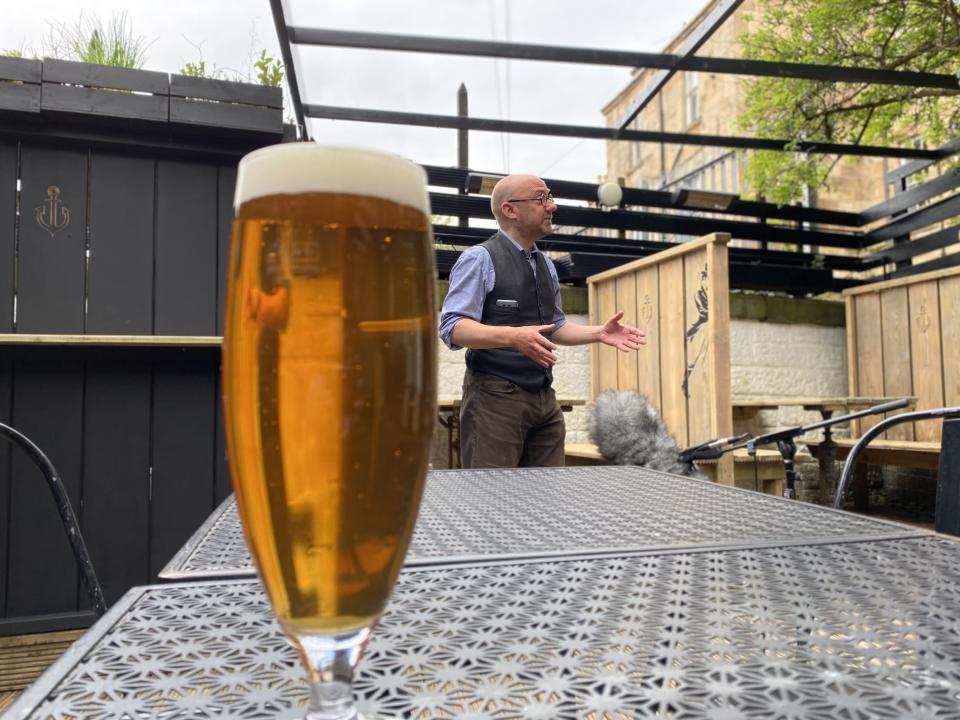 Patrick Harvie speaking in the background of a pint of beer