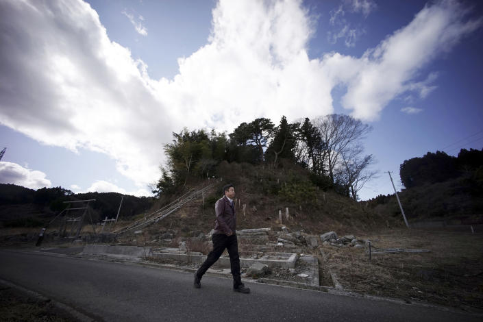 FILE - In this March 5, 2015, file photo, Michihiro Kono, president of Yagisawa Shoten Co., walks by a hill where his company's employees ran up to a shrine for safety when the 2011 tsunami hit Rikuzentakata, Iwate Prefecture, northeastern Japan. Just a month after a tsunami smashed into the city of Rikuzentakata, Kono took over his family's soy sauce business. (AP Photo/Eugene Hoshiko, File)