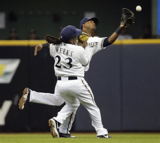 Milwaukee Brewers' Jean Segura and Rickie Weeks (23) can't come up with a ball hit by Los Angeles Dodgers' Matt Kemp during the sixth inning of a baseball game Wednesday, May 22, 2013, in Milwaukee. (AP Photo/Morry Gash)