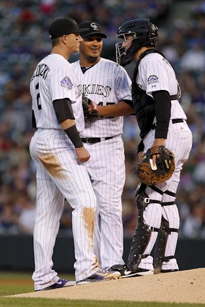 Colorado Rockies starting pitcher Jhoulys Chaci, center, stands on the mound with teammates Troy Tulowitzki , left, and catcher Jordan Pacheco, right, during the third inning of a baseball game against the Arizona Diamondbacks, Friday, Sept. 20, 2013, in Denver. (AP Photo/Barry Gutierrez)