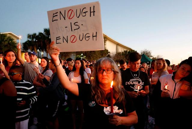 <p>Mourners stand during a candlelight vigil for the victims of Marjory Stoneman Douglas High School shooting in Parkland, Fla., on Feb. 15, 2018. (Photo: Rhona Wise/AFP/Getty Images) </p>
