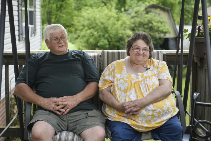 """Doris Kelly, 57, sits with her husband, Tom Grimm, 62, on the front porch of their home on Monday, June 29, 2020 in Ruffs Dale, Pa. Kelly was one of the first patients in a UPMC trial for COVID-19. """"It felt like someone was sitting on my chest and I couldn't get any air,"""" Kelley said of the disease. (AP Photo/Justin Merriman)"""