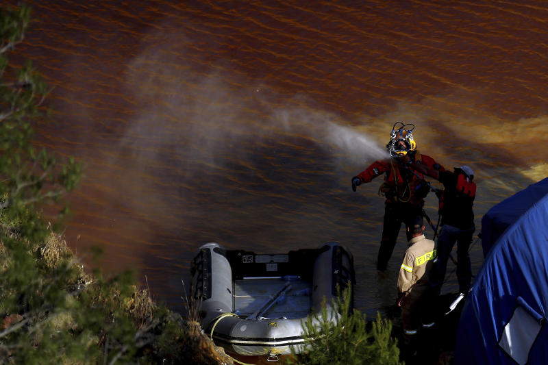 A man is sprayed clean with water after a dive in a toxic man-made lake during a search for a third suitcase near the village of Mitsero outside of the capital Nicosia, Cyprus, Tuesday, May 7, 2019. New police chief Kypros Michailides has apologized to the families of seven foreign women and girls who an army captain has confessed to killing. (AP Photo/Petros Karadjias)