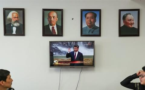 Framed portraits of German philosopher Karl Marx, Soviet state founder Vladimir Lenin and China's late leaders Mao Zedong and Deng Xiaoping hung above a screen showing a news broadcast of China's President Xi Jinping - Credit: Reuters