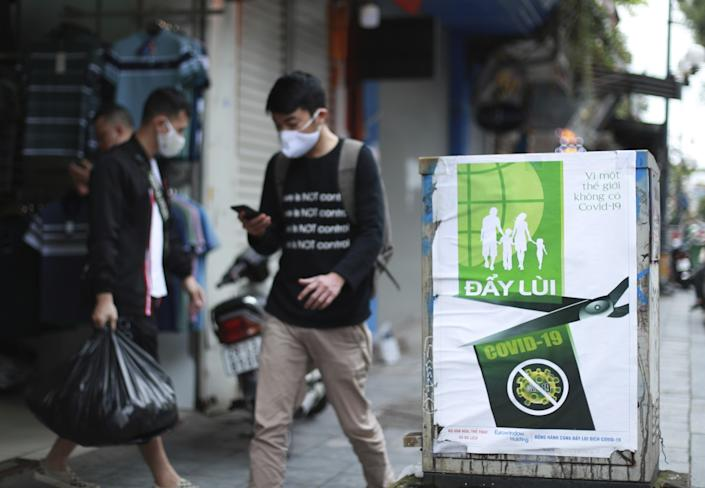 """A poster in Hanoi reads """"Fighting COVID-19,"""" in Vietnamese. Many business activities resumed Thursday as Vietnam lifted a nationwide lockdown to contain the spread of COVID-19. <span class=""""copyright"""">(Hau Dinh / Associated Press)</span>"""