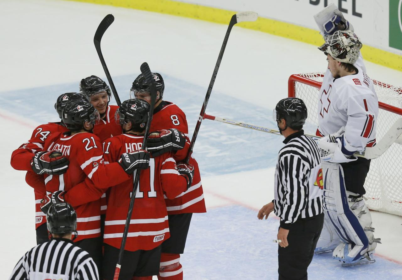 Canada celebrates a goal by Griffin Reinhart (8) in front of Switzerland's goalie Melvin Nyffeler during the first period of their IIHF World Junior Championship ice hockey game in Malmo, Sweden, January 2, 2014. REUTERS/Alexander Demianchuk (SWEDEN - Tags: SPORT ICE HOCKEY)