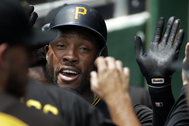 Pittsburgh Pirates' Starling Marte is greeted in the dugout after hitting a solo home run off Milwaukee Brewers starting pitcher Chase Anderson in the first inning of a baseball game in Pittsburgh, Saturday, July 14, 2018. (AP Photo/Gene J. Puskar)