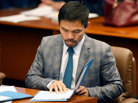 Philippine Senator and boxing champion Manny Pacquiao reads his briefing materials as he prepares for the Senate session in Pasay city, Metro Manila, Philippines September 20, 2016. Picture taken September 20, 2016.    REUTERS/Erik De Castro