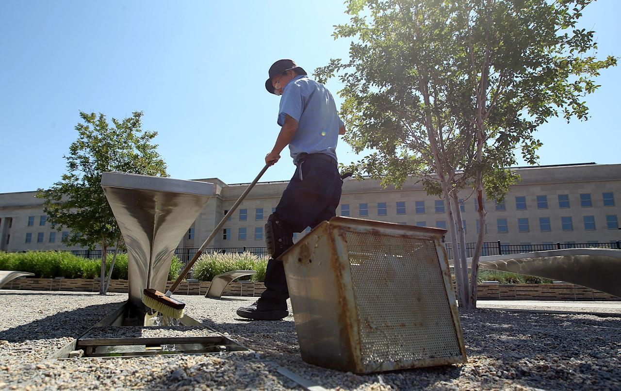 ARLINGTON, VA - JUNE 28:  Groundskeeper Lucas Guzman washes the glowing light pool of a bench at the Pentagon Memorial June 28, 2011 in Arlington, Virginia. This year is the 10th anniversary of the September 11 terrorist attacks, in which 184 people were killed at the Pentagon.   (Photo by Alex Wong/Getty Images)
