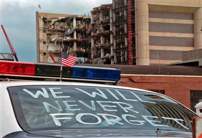 """In this April 24, 1995 photo, an Oklahoma City police car decorated with the words, """"We will never forget"""" and a small American flag sits near the Alfred P. Murrah Federal Building in Oklahoma City. The American terrorist who set the blast killed 168 people, including 19 children. Life changed in the U.S. in its aftermath, with a new attention paid to domestic terrorism and beefed up security at federal buildings around the country."""