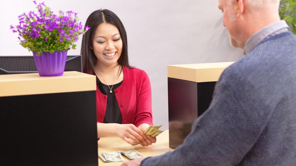 An adult man bank customer making a financial transaction with a bank teller over the counter in a retail bank.