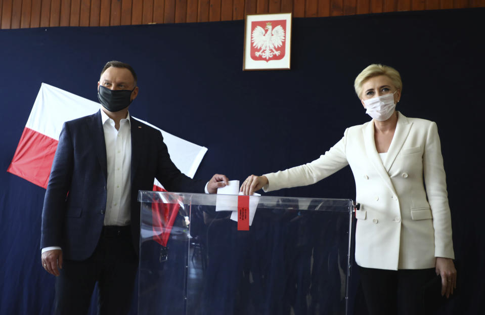 FILE - In this June 28, 2020, file photo, Poland's President Andrzej Duda and his wife Agata Kornhauser-Duda cast their vote during presidential election in Krakow, Poland. Duda and Warsaw Mayor Rafal Trzaskowski are heading into a tight presidential runoff that is seen as an important test for populism in Europe. The Sunday, July 12 election comes after a bitter campaign that has exacerbated a conservative-liberal divide in the country. (AP Photo/Beata Zawrzal, File)