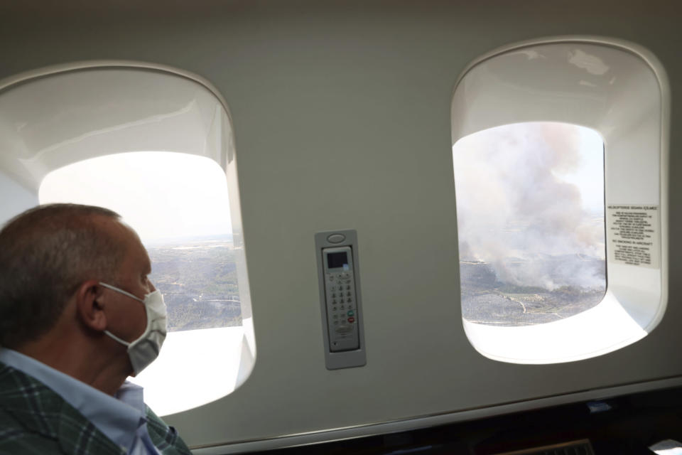 Turkey's President Recep Tayyip Erdogan watches from his plane the wildfires in Manavgat, Antalya, Turkey, Saturday, July 31, 2021. The death toll from wildfires raging in Turkey's Mediterranean towns rose to six Saturday after two forest workers were killed, the country's health minister said. Fires across Turkey since Wednesday burned down forests, encroaching on villages and tourist destinations and forcing people to evacuate.(Turkish Presidency via AP, Pool)