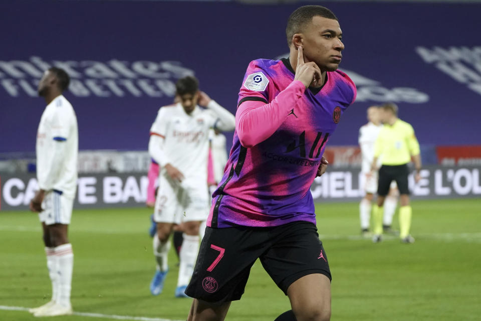 Paris Saint Germain's Kylian Mbappe celebrates after he scored a goal against Lyon during the French League One soccer match between Lyon and PSG in Decines, near Lyon, central France, Sunday, March 21, 2021. (AP Photo/Laurent Cipriani)