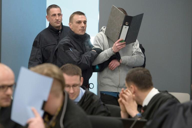 Two of the defendants cover their faces at the start of their trial in Dresden, eastern Germany, on March 7, 2017