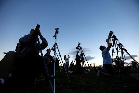 """People watch the solar eclipse over Carhenge in Alliance, Neb., U.S. August 21, 2017. Location coordinates for this image are 42°8'33""""N 102°51'29""""W. REUTERS/Scott Morgan"""